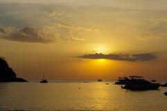 在水的惊人的热带橙色日落,与岩石剪影和一条小船在普吉岛海岛上,泰国 库存图片
