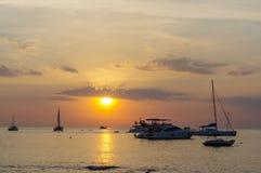 在水的惊人的热带橙色日落,与岩石剪影和一条小船在普吉岛海岛上,泰国 免版税图库摄影