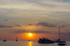 在水的惊人的热带橙色日落,与岩石剪影和一条小船在普吉岛海岛上,泰国 图库摄影