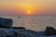 在水的惊人的热带橙色日落,与岩石剪影和一条小船在普吉岛海岛上,泰国 免版税库存照片