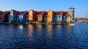 在水的意想不到的五颜六色的大厦在蓝色小时,格罗宁根,荷兰 库存照片