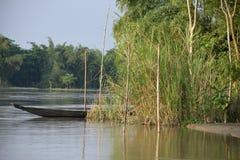 在水的河船,掩藏在竹子后 库存照片
