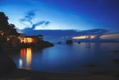 在水的热带平房在晚上 免版税库存照片