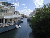 在水的白色和蓝色加勒比房子 免版税库存照片