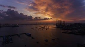 在水的美好,惊人的日落,在一个工业看的船坞或口岸的小船 免版税库存图片