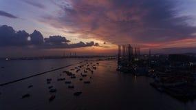 在水的美好,惊人的日落,在一个工业看的船坞或口岸的小船 免版税库存照片