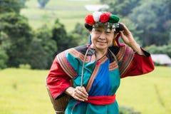 在水稻领域五颜六色的服装礼服的愉快的小山部落微笑 图库摄影