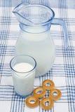 在水罐和玻璃的牛奶用百吉卷 免版税库存图片