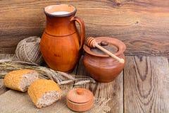 在水罐和面包的健康土气早餐牛奶在木桌上 图库摄影
