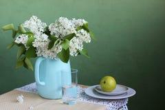 在水罐的开花的白色丁香 在土气样式的静物画 免版税库存图片