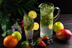 在水罐的Mojito柠檬水和玻璃和果子在黑暗的木背景 免版税库存图片