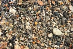 在水表面照片背景下的小小卵石小卵石 免版税库存照片