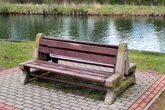 在水运河附近的空的长凳 免版税图库摄影