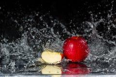 在水飞溅的两个红色苹果 免版税图库摄影