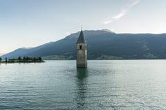 在水,被淹没的村庄,山下的教会在背景中环境美化和峰顶 Reschensee湖Reschen Lago di Resia 免版税库存照片