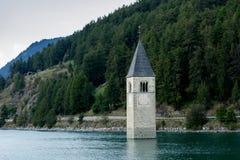 在水,被淹没的村庄,山下的教会在背景中环境美化和峰顶 Reschensee湖Reschen Lago di Resia 库存照片