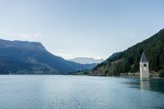 在水,被淹没的村庄,山下的教会在背景中环境美化和峰顶 Reschensee湖Reschen Lago di Resia 免版税图库摄影