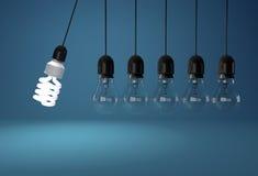 在永恒运动的节能和白炽电灯泡在蓝色 免版税库存图片