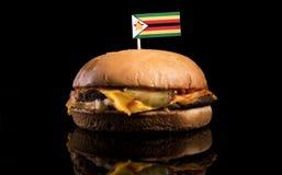 在汉堡包顶部的津巴布韦旗子在黑色 库存照片