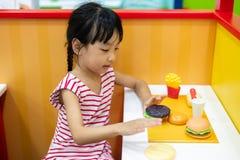 在汉堡商店的亚洲中国小女孩角色扮演 库存图片