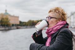 在江边的妇女饮用的咖啡 免版税库存照片