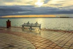 在江边的铁长凳日落的 库存照片