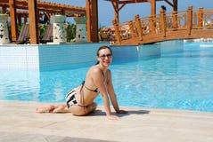 在池坐的微笑的游泳妇女附近 免版税库存图片