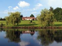 在池塘反映的之家 库存照片