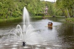 在池塘和浮动鸭子房子中间的喷泉在美丽如画的公园 图库摄影