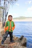 在池塘坚持附近的男孩 免版税库存图片