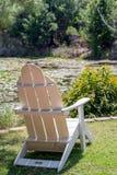 在池塘旁边的椅子 免版税库存照片