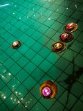 在池塘水、佛教细节和背景的美好和五颜六色的浮动蜡烛 免版税库存照片