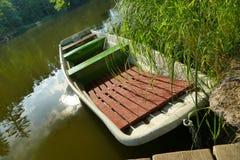 在池塘的一条老小船 免版税库存图片