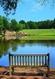 在池塘的公园长椅 免版税库存照片
