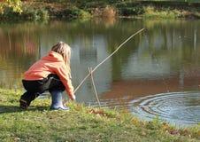 在池塘的女孩捕鱼 免版税库存照片