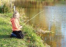 在池塘的女孩捕鱼 库存图片