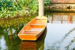 在池塘的小木小船 免版税库存照片