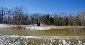 在池塘的斯诺伊银行的木客舱 免版税库存照片