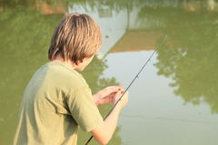 在池塘的男孩捕鱼 库存照片