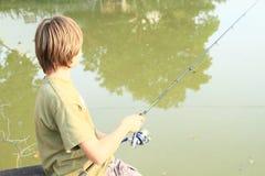 在池塘的男孩捕鱼 库存图片
