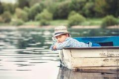 在池塘的老小船的小男孩夏天晚上 免版税库存图片