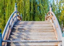在池塘的被风化的木弯曲的桥梁 库存照片