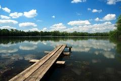 在池塘的长凳 免版税库存照片
