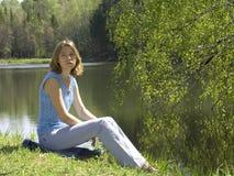 在池塘选址附近的女孩 免版税库存图片
