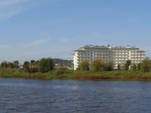 在池塘银行的旅馆大厦在绿地 库存照片