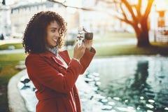在池塘附近的卷曲妇女有葡萄酒照相机的 库存照片