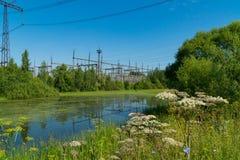 在池塘附近的发电站 查出的拉长的现有量排行次幂白色 免版税库存图片