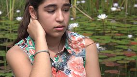 在池塘附近的哀伤的十几岁的女孩 影视素材