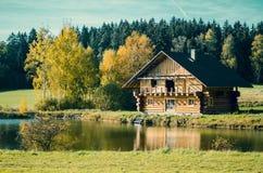 在池塘附近的秋天木客舱 免版税库存照片