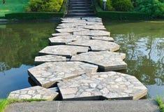 在池塘间的石路径 免版税库存图片